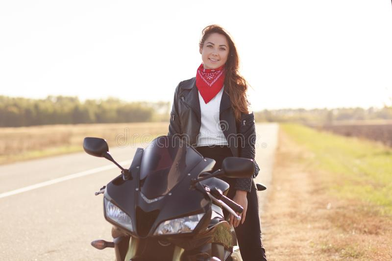 Shot of pleasant looking woman biker sits on fast black motorbike, wears red stylish bandana and leather jacket, travels alone, pr. Epares for motorcycling royalty free stock photo