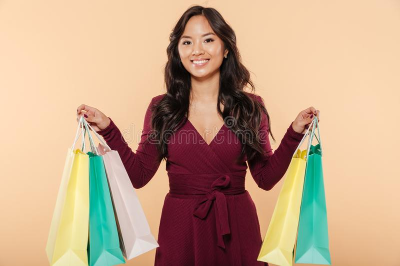 Shot of pleased asian female in pretty maroon dress posing over. Beige background, holding packs with purchases after shopping royalty free stock photography