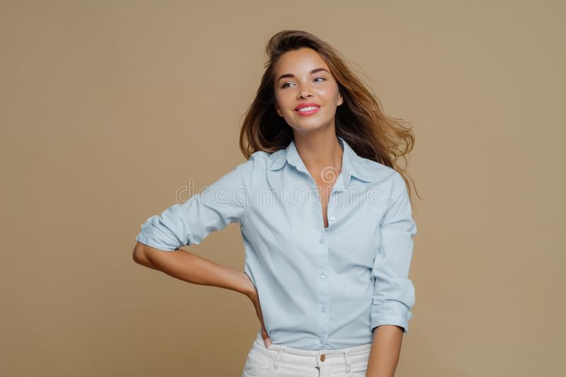 Shot of pretty cheerful European woman keeps one hand on waist, looks aside, has charming smile wears shirt and trousers, has slim royalty free stock photos