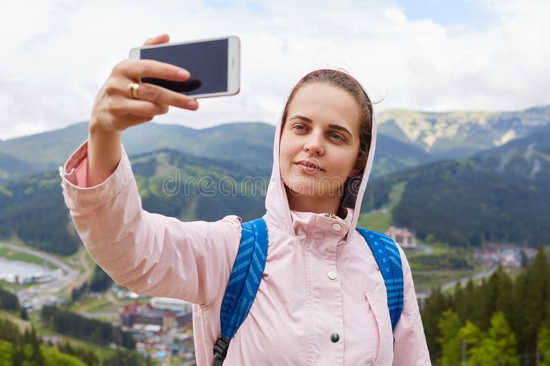 Shot of pretty young female tourist makes selfie in mountain, woman traveler being photographed outdoor against beautiful. Landscape. Traveling, lifestyle stock photos