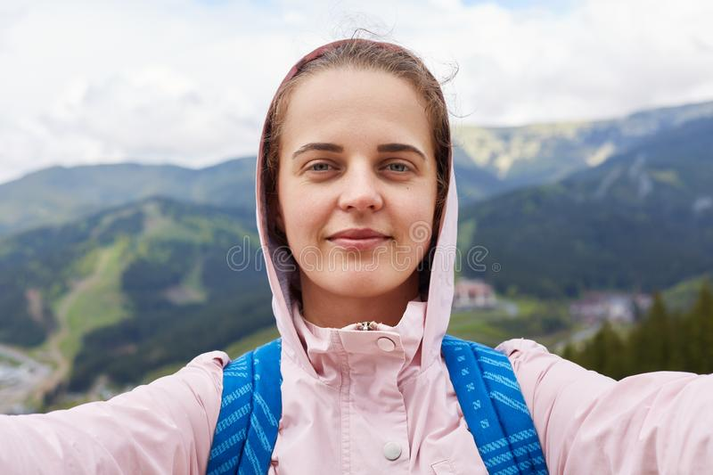 Shot of pretty young female tourist makes selfie in mountain. Woman traveler having active recreation in mountains. Travel,. Tifestyle, adventure, active stock photography