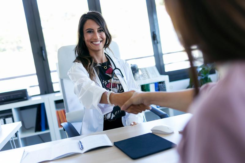 Pretty young obstetrician gynecologist and pregnant woman shaking hands in the first visit in the clinic. Shot of pretty young obstetrician gynecologist and stock photography