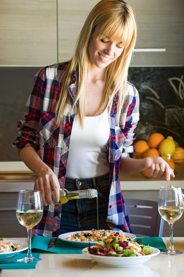 Pretty young woman dressing quinoa salad in the kitchen at home. stock image