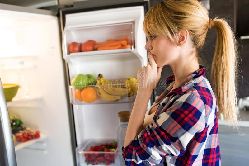 Pretty young woman hesitant to eat in front of the fridge in the kitchen. stock image