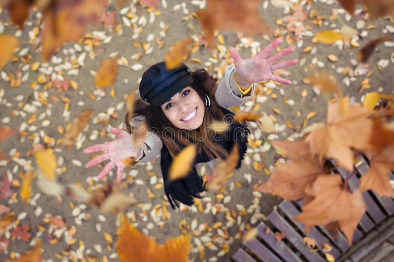Pretty young woman looking to the sky with arms raised as leaves fall from the trees in the park in autumn stock image