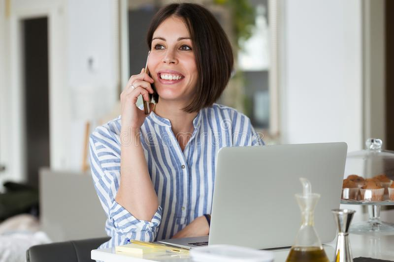 Pretty young woman using her mobile phone while working with laptop at home stock photos