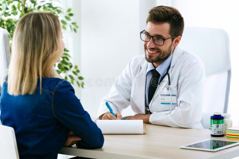 Pretty young woman talking with handsome young doctor about her health in the consultation. royalty free stock photo