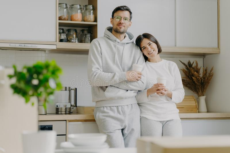 Shot of relaxed family couple stand in kitchen, drink takeaway coffee, wear casual outfit, pose in kitchen interior, bought new stock images