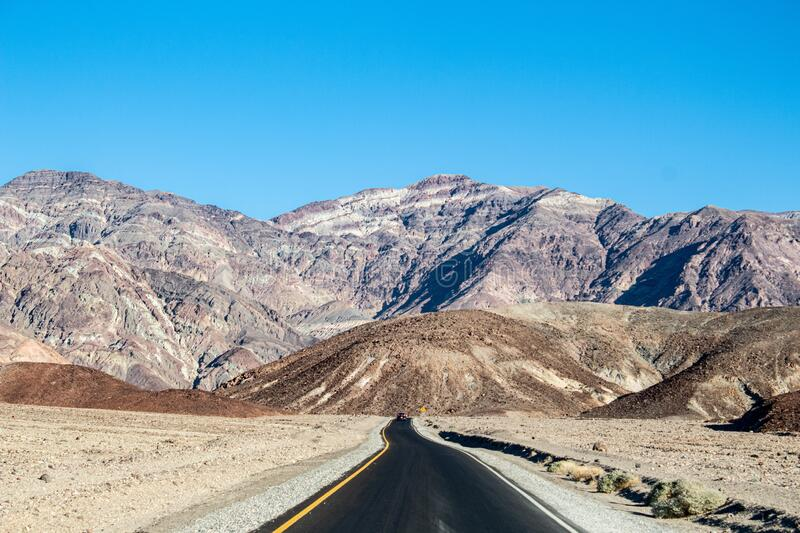 Shot of a  road  near the massive mountains in Death Valley National Park, California USA royalty free stock images