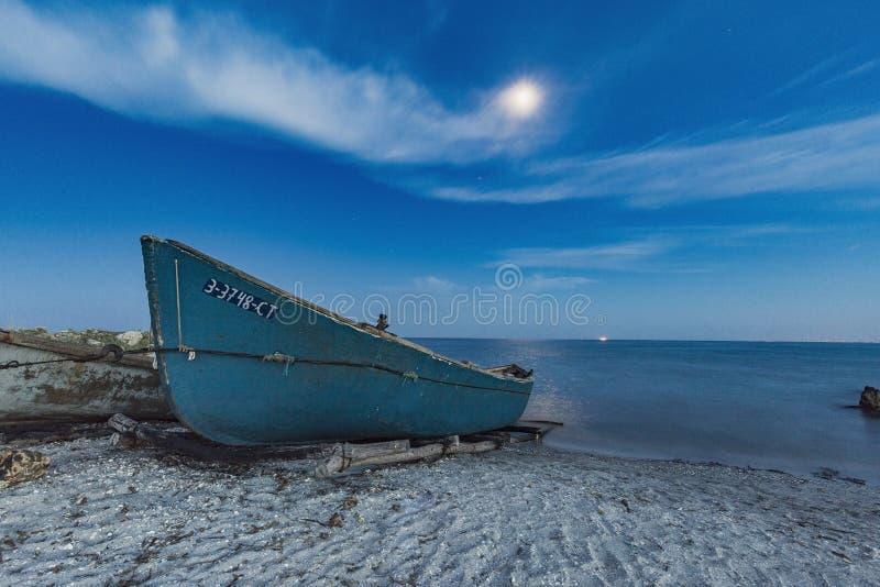Boat in the moonlight night, shot on Romania seaside royalty free stock photo