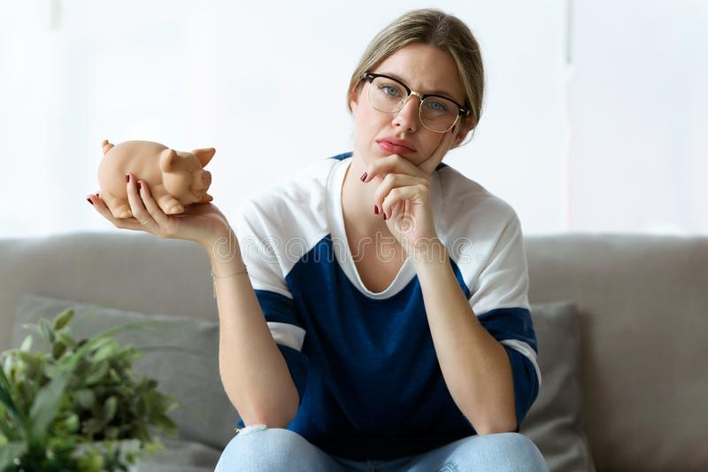 Sad young woman looking at camera while holding her piggy bank at home. Shot of sad young woman looking at camera while holding her piggy bank at home royalty free stock photo