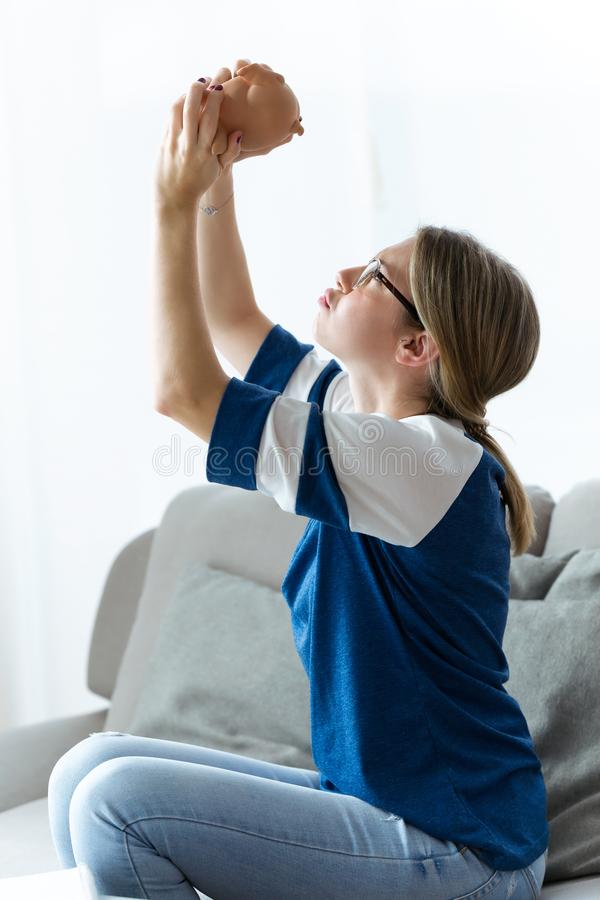 Sad young woman looking and holding her piggy over her head on sofa at home. Shot of sad young woman looking and holding her piggy over her head on sofa at home stock photo