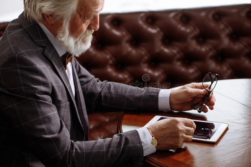 Shot of senior business man looking at the screen of the tablet royalty free stock photos