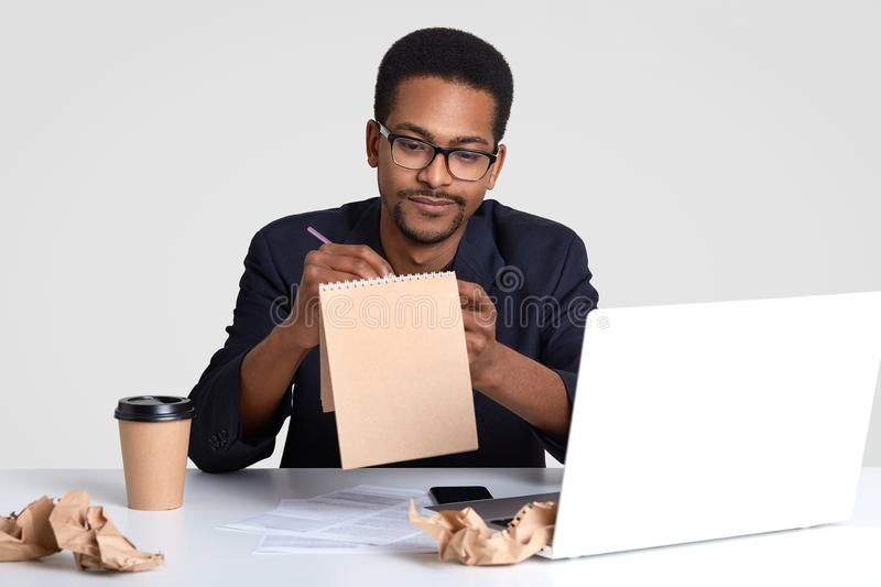 Shot of serious black man journalist works on creation new article, writes down ideas in spiral notepad, works in laptop computer. Surrounded with papers royalty free stock photo