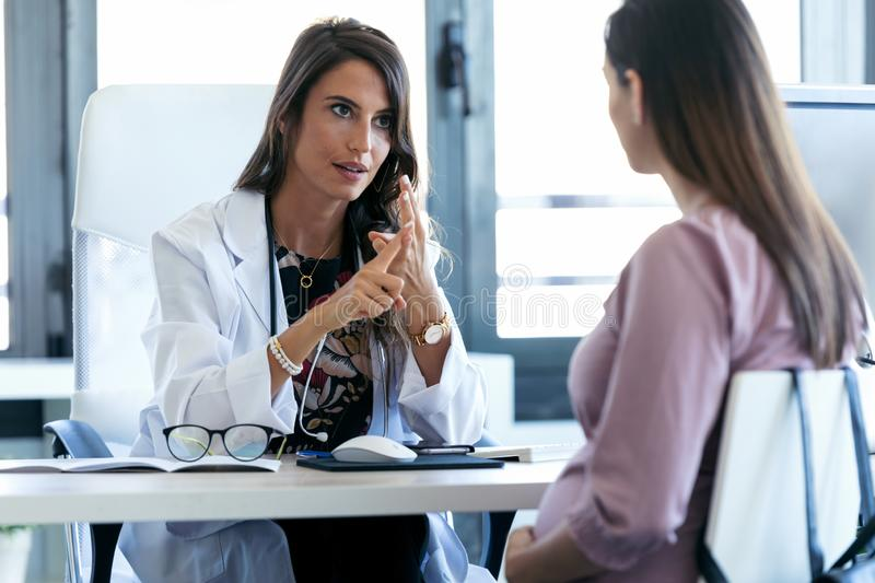 Serious young gynecologist giving guidelines to his pregnant patient in the clinic royalty free stock photo