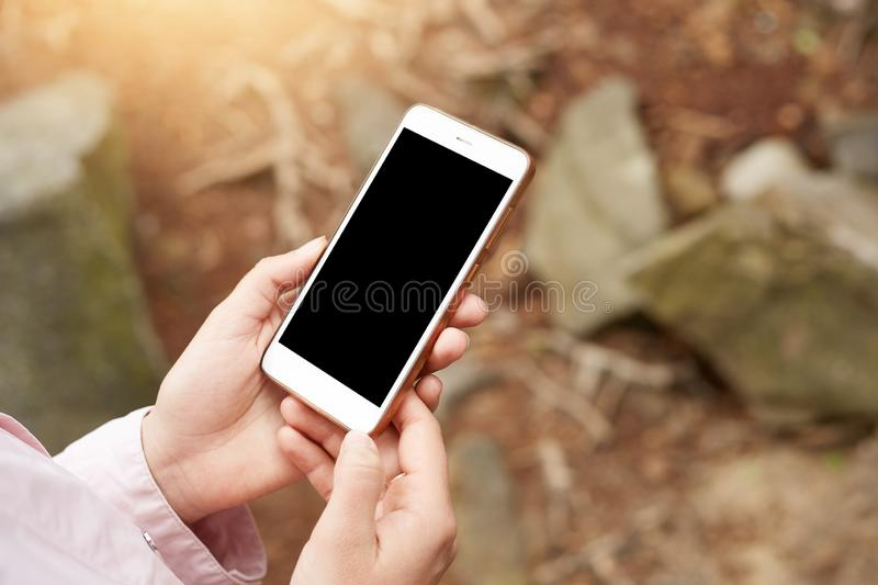 Shot of smartphone be held in both hands in front of stones and forest plants, screen of device is block, mobile phone is out of stock image