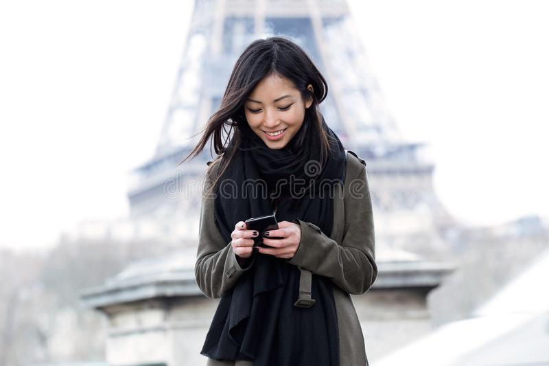 Smiling asian young woman using her mobile phone in front of Eiffel tower. stock image