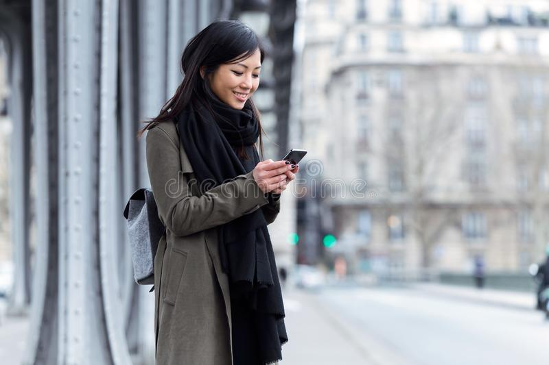 Smiling asian young woman using her mobile phone in the street. stock images