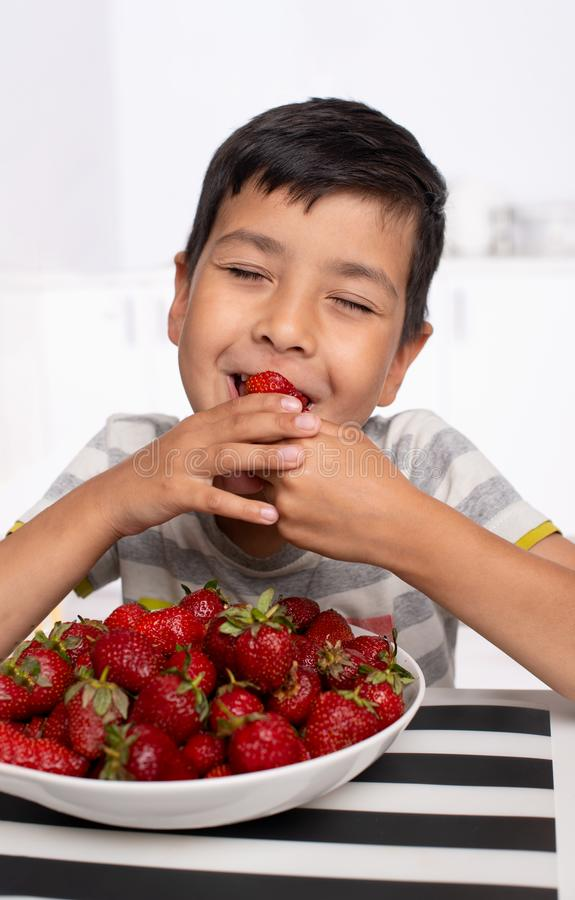 Shot of a smiling boy sitting in the kitchen eating strawberries with closed  eyes from pleasure stock photo