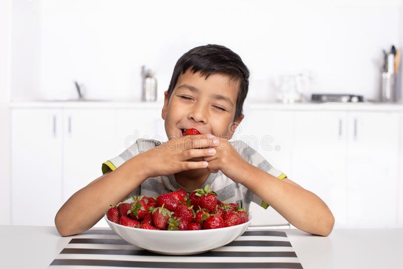 Shot of a smiling boy sitting in the kitchen eating strawberries with closed  eyes from pleasure stock image