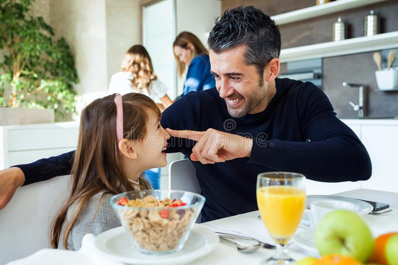 Smiling cute father and daughter having fun while having breakfast in family in the kitchen at home royalty free stock photos