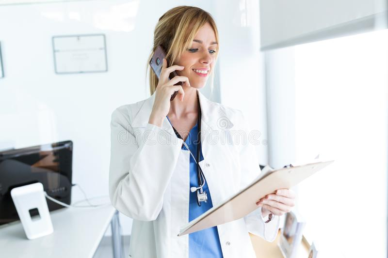 Smiling female doctor using her mobile phone while reviewing some papers in the consultation. Shot of smiling female doctor using her mobile phone while stock photography