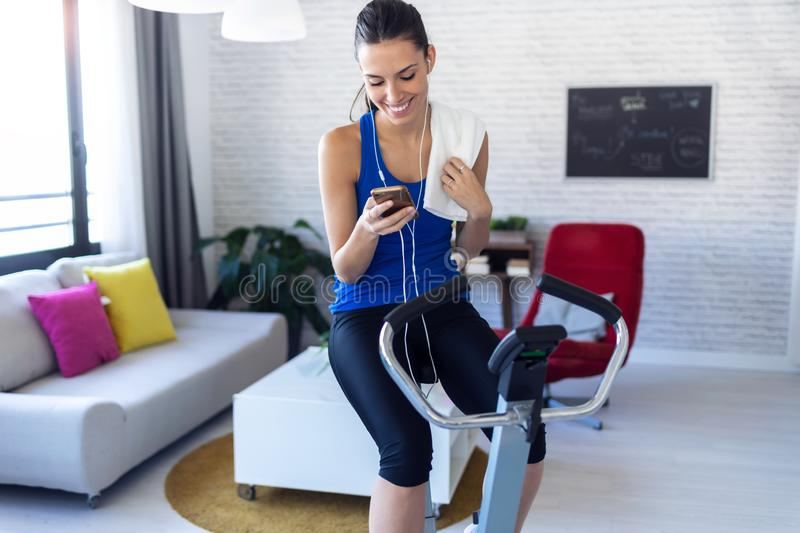 Smiling fitness girl using mobile phone after training on exercise bike at home royalty free stock photos