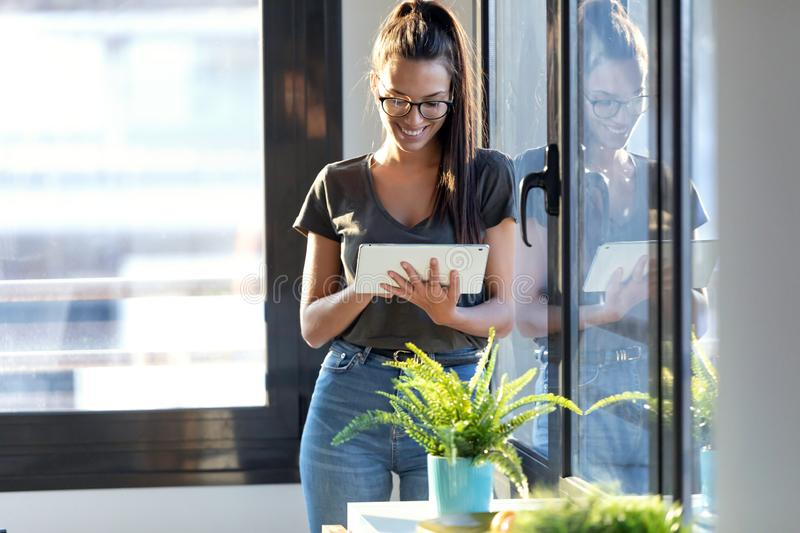Smiling young business woman using her digital tablet while standing next to the window in the office royalty free stock photo
