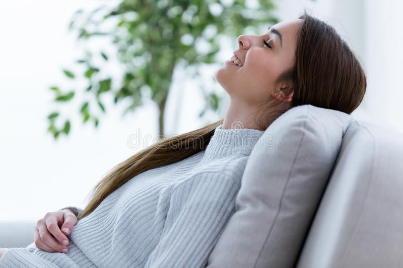 Smiling young woman relaxing on sofa at home. stock image