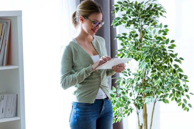 Smiling young woman using her digital tablet at home. stock photos