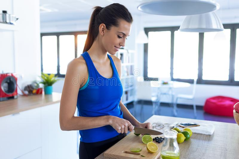 Sporty young woman cutting limes while listening to music in the kitchen at home stock images