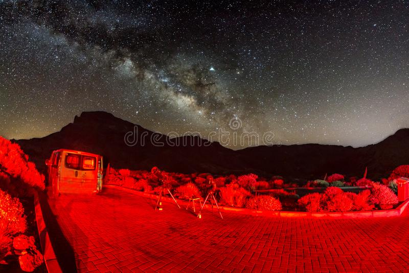 Shot of stars and milky way at hight sky via fish eye lens. Two telescopes ready for observation lit by the rear lights of the car stock photography