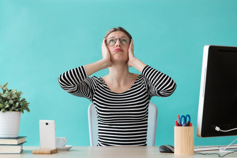 Stressed young woman holding her head and looking to up while working in the office stock photos