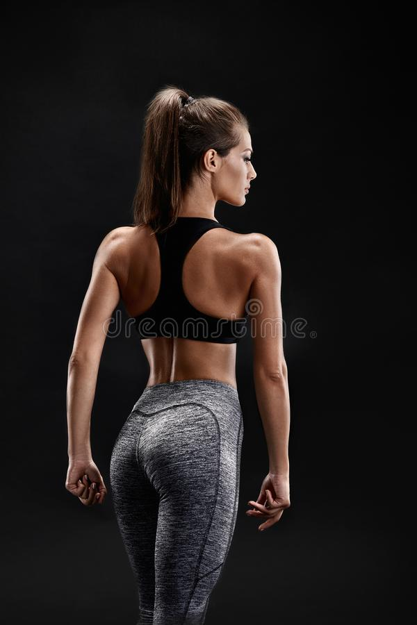 Shot of a strong woman with muscular abdomen in sportswear. Fitness female model posing on black background. stock images