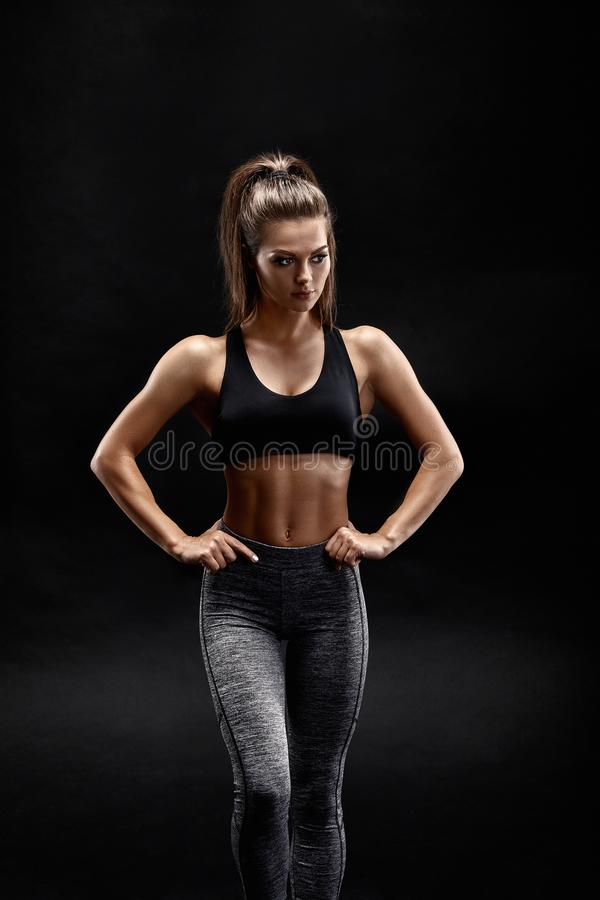 Shot of a strong woman with muscular abdomen in sportswear. Fitness female model posing on black background. stock image