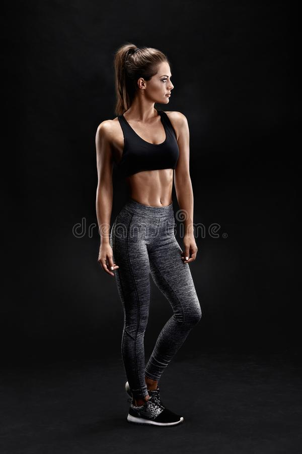 Shot of a strong woman with muscular abdomen in sportswear. Fitness female model posing on black background. stock photos