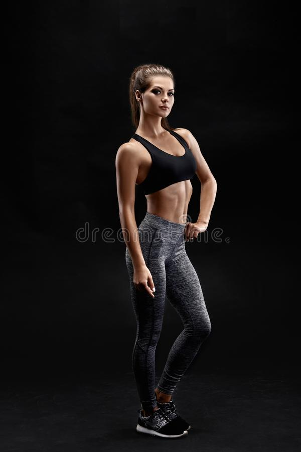 Shot of a strong woman with muscular abdomen in sportswear. Fitness female model posing on black background. royalty free stock image
