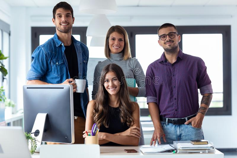 Successful business team posing grouped around an attractive young woman looking at the camera in the coworking space royalty free stock photo