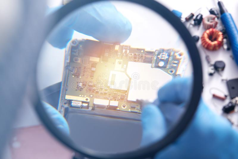 Shot of table full of electronic parts of pc. Analysis computer ram through magnifying glass, faceless repairman working in lab,. Desktop with broken stock photography