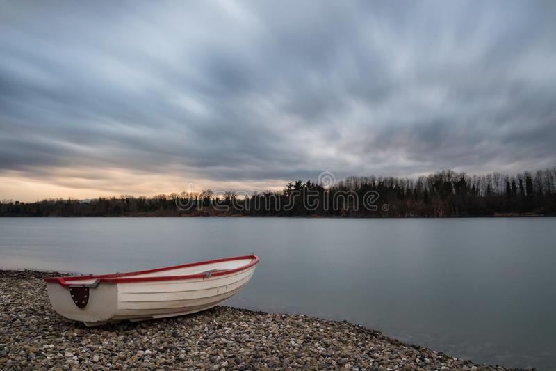 Shot taken at a lake at sunset on a cloudy day. On the first floor a moored boat royalty free stock photography