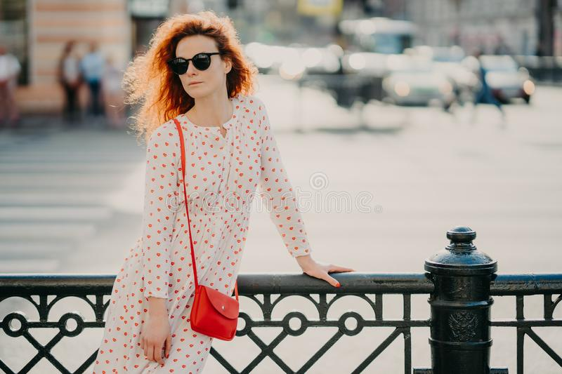 Shot of thoughtful red haired curly woman focused aside, wears long white dress, poses near black hence at street against blurred royalty free stock image