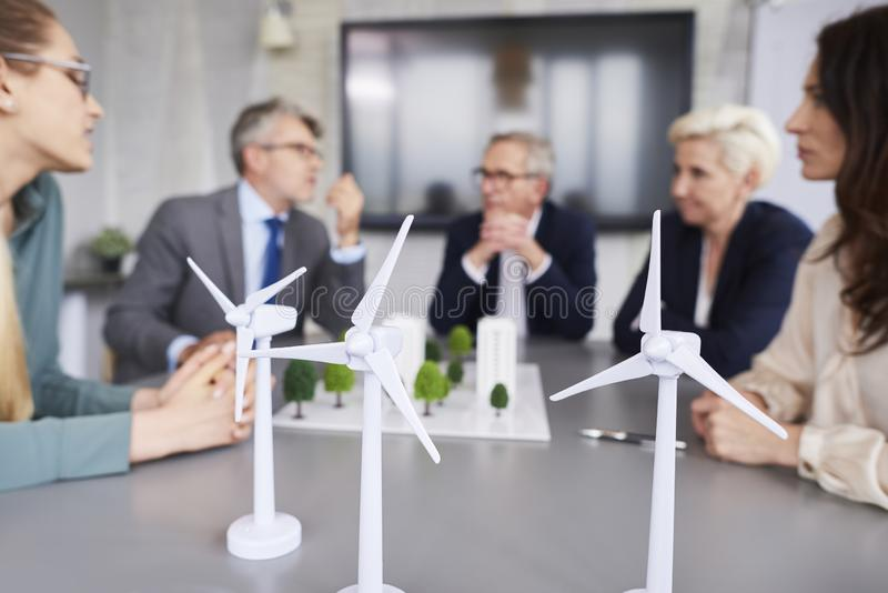 Shot of three wind turbines. And business people in the office royalty free stock photo