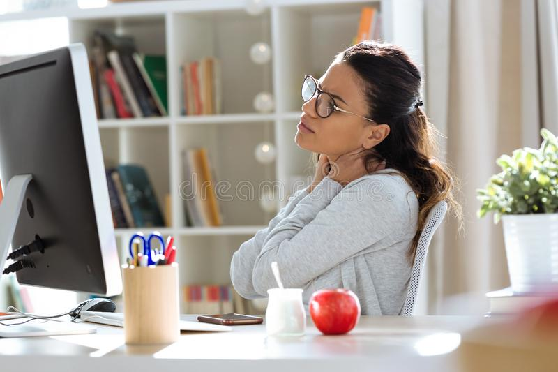 Tired young business woman having neck and back pain while working with computer in the office royalty free stock photos