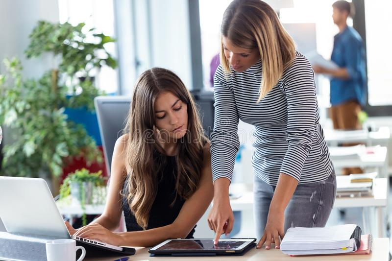 Two business young women working together with digital tablet in the modern startup office. Shot of two business young women working together with digital tablet royalty free stock photo