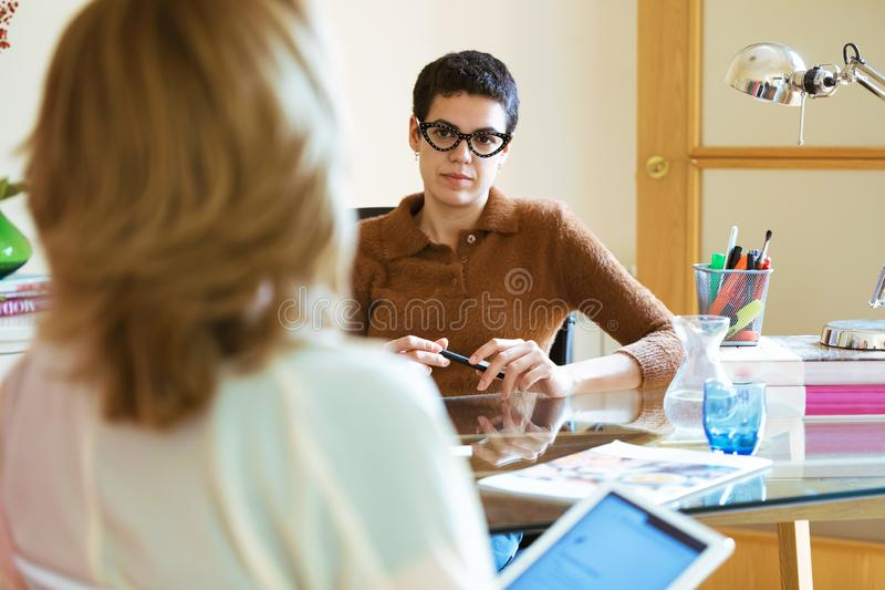 Two businesswomen talking about work and exchanging ideas with digital tablet in the office. Shot of two businesswomen talking about work and exchanging ideas royalty free stock photo