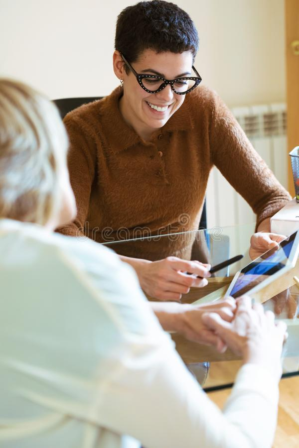 Two businesswomen talking about work and exchanging ideas with digital tablet in the office. Shot of two businesswomen talking about work and exchanging ideas stock images