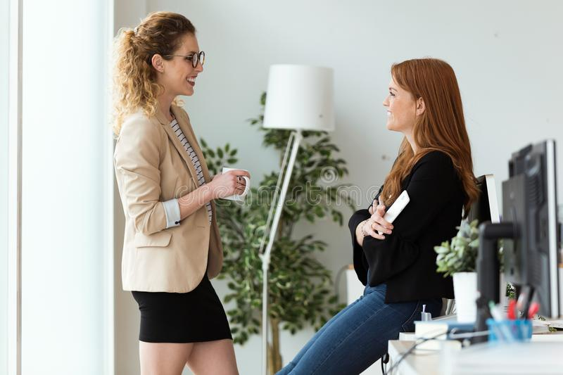 Two pretty young business woman relaxing one moment while drinking coffee in the office. stock photos