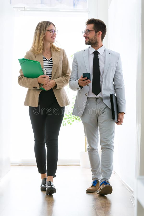 Two young business partners walking and talking through the office. stock photography