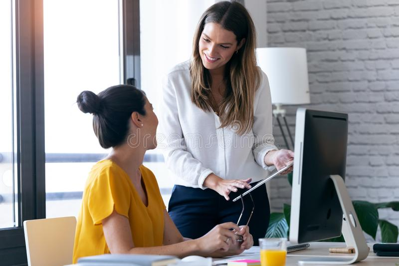 Two young businesswomen talking and reviewing they last work in the digital tablet in the office royalty free stock images