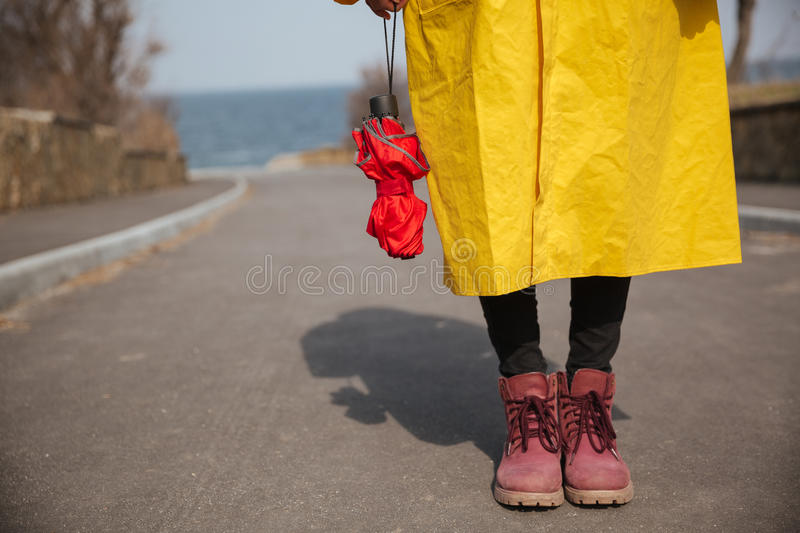 Shot of umbrella and woman legs. Close up photo of woman legs while she holding red closed umbrella royalty free stock image